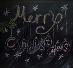 holiday decoration/ Merry Christmas inscription painted by with chalk on blackboard with stars and balls