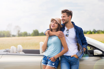 Young couple standing near convertible