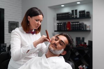 The barber woman carefully shaves beard with razor