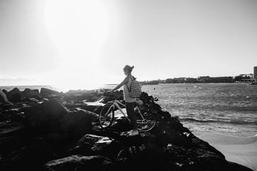Young woman with backpack standing on the shore near his bike an