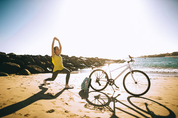 Young women is engaged in yoga on sunset with bike