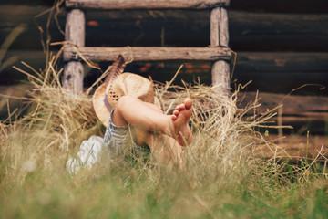 Barefoot boy sleeps on the grass near ladder in haystack