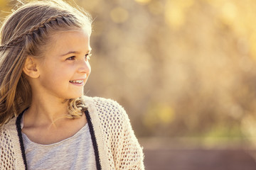 Beautiful Portrait of smiling little girl outdoors. View from the side with girl looking forward