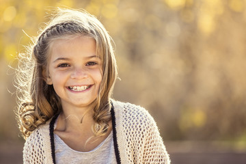 Beautiful Portrait of smiling little girl outdoors. Taking a cute picture