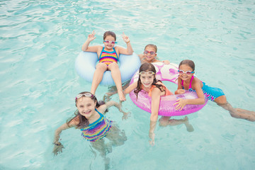 Group of cute little girls playing at an outdoors swimming pool on a warm summer day. Smiling little girls in their swimming suits