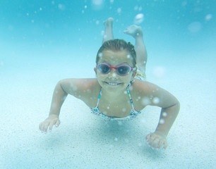 Cute smiling little girl swimming underwater in an outdoor swimming pool