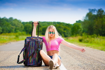 Girl in road suitcase, pink t-shirt, blue shorts, full height