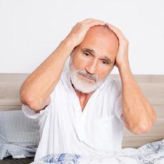 Elderly man sitting on bed suffering from headache