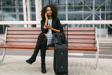 Confident African American businesswoman using cell phone in airport with her suitcase