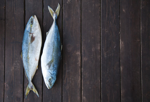 Fresh Fish on wooden background. Yellowtail Amberjack