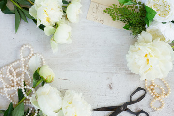 White fresh peony flowers with pearls jewellery on white wooden desktop frame with copy space