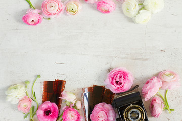 Pink and white ranunculus flowers with retro camera flat lay scene, copy space on wooden desktop