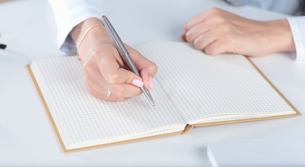 Female hand writes with a pen in a diary notebook.