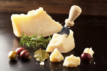 Parmesan cheese with olives and rosemary