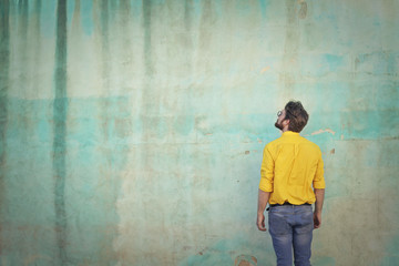 Man with yellow shirt looking at the wall
