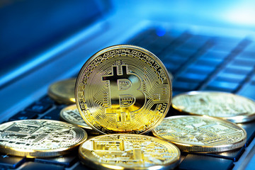 Photo Golden Bitcoins (new virtual money ) close-up on a blue background with a computer keyboard.