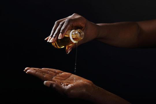 mains femme noire s'enduisant d'huile de baobab