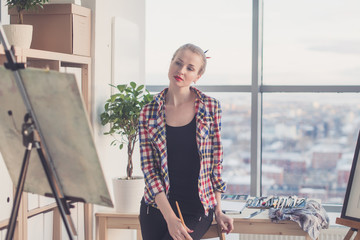 Female painter standing in workshop, watching at drawing attentively, holding paintbrush. Artist looking on picture concentrated, front view portrait.