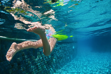 Funny underwater photo of baby girl swimming with fun on yellow ring in clear blue aqua park pool. Healthy family lifestyle, children water sports activity and fitness with parents on summer vacation.