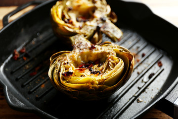 Baked artichokes on black grill pan, close up