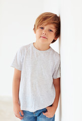 portrait of handsome young boy, kid posing near the white wall
