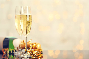 Two champagne glasses and bottle on light background