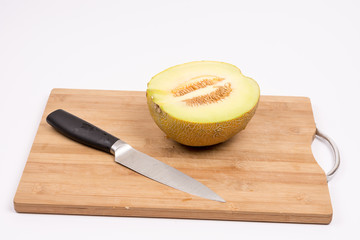 Sliced half melon and knife on the wooden board with copy space