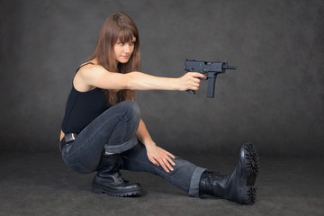 Young woman shoots from pistol sitting on one leg