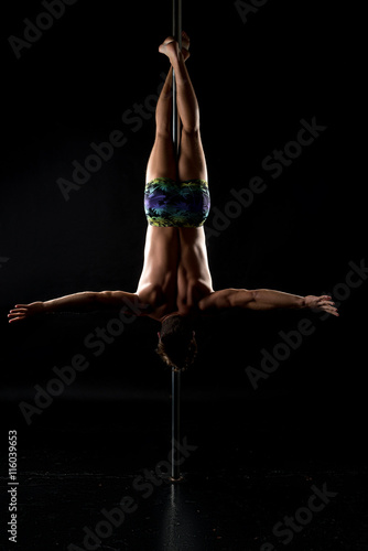 pole dance shot of strong man hanging upside down stock photo and
