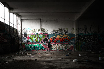 Hooded boy finishing graffiti in disused warehouse