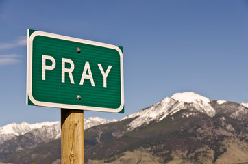 Pray Sign with snow-covered Mountains in the background Wall mural