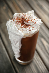 Iced coffee with cream on wooden table