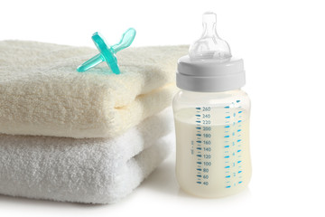 Baby bottle with milk and soft towels isolated on white