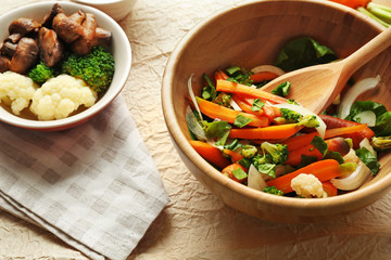 Salad with baby carrot in wooden bowl closeup