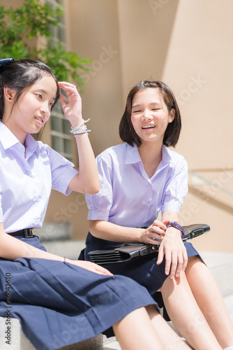 cute asian thai high schoolgirls student couple in school uniform sit on the stairway chatting. Black Bedroom Furniture Sets. Home Design Ideas