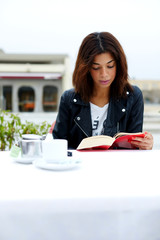 Young lovely female enjoying a good book while sitting in coffee shop