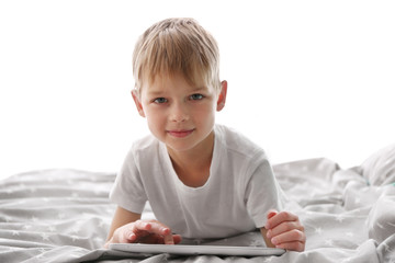 Cute little boy playing with tablet on bed
