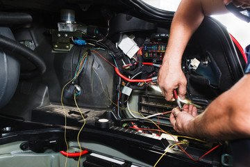 Electrician works with electric block in car. Close-up of automobile inside under raised hood. Service man hands working with cables of auto Wall mural