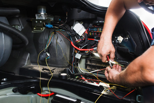 Electrician works with electric block in car. Close-up of automobile inside under raised hood. Service man hands working with cables of auto