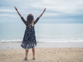 Young woman raising her arms on the beach