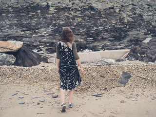 Young woman walking on a pebble beach