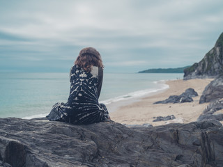 Woman sitting on rocks by the sea