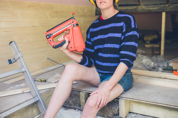 Young woman with nail gun in loft conversion
