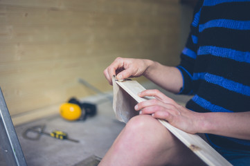 Young woman sanding cladding