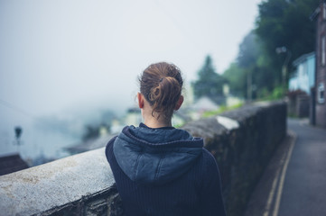 Young woman standing by wall in fog