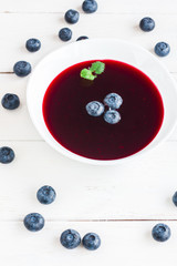 blueberry soup on wooden white background, top view