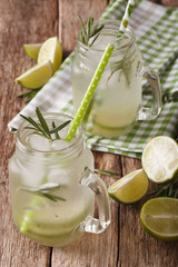 Cold lemonade with lime, ice and rosemary close up in a glass jar. vertical