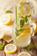 Classic lemonade with ice and mint close up on the table. vertical