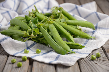 Fresh green peas on rustic wooden background, selective focus