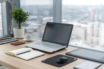 Sideview of office desktop with blank laptop and various tools. Wall mural
